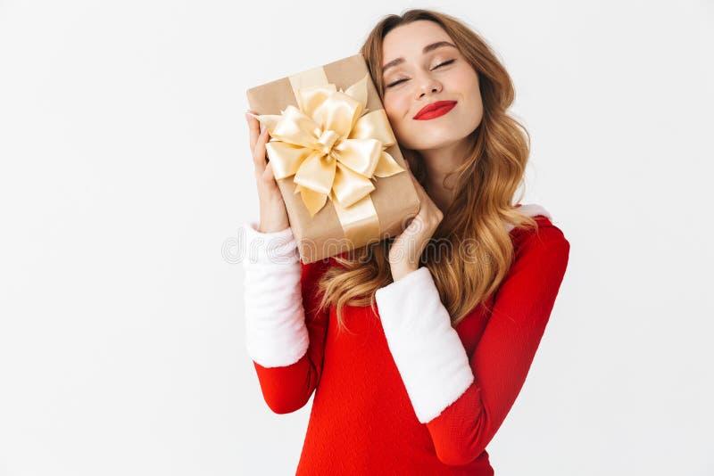 Retrato da mulher bonito 20s que veste o traje vermelho de Santa Claus que sorri e que guarda a caixa de presente, isolado sobre  foto de stock