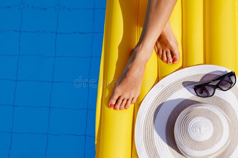 Retrato da mulher bronzeada bonita que relaxa no biquini na piscina Os p?s fecham-se acima Pedicure vermelho polonês do gel Dia d fotos de stock royalty free