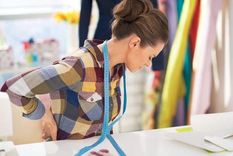 Retrato da mulher cansado do alfaiate com dor nas costas imagem de stock