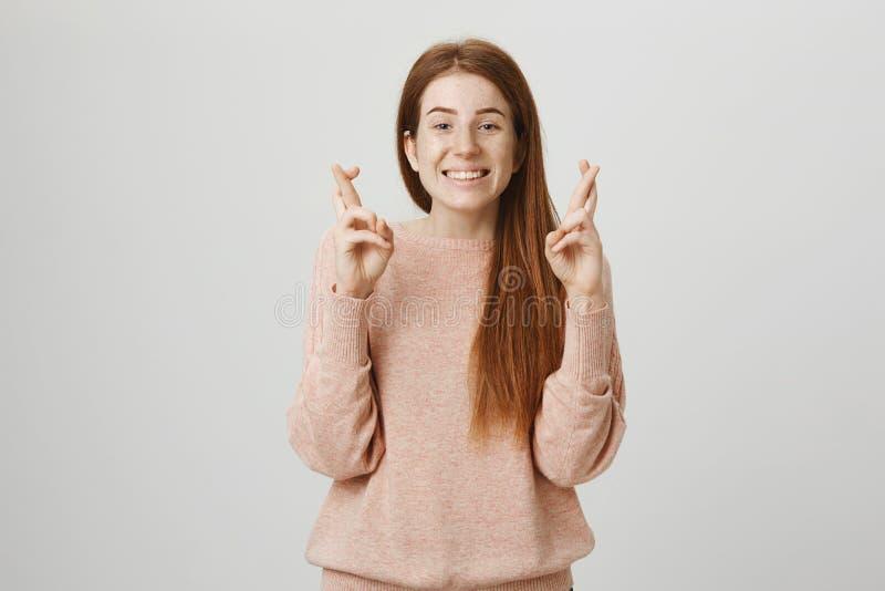 Retrato da mulher caucasiano do ruivo entusiasmado feliz que está com os dedos cruzados aumentados que desejam algo ou rezar fotos de stock royalty free