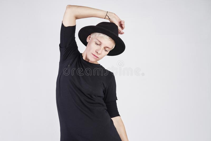 Retrato da mulher caucasiano loura que veste a roupa preta e o chapéu que levantam no fundo branco imagem de stock royalty free
