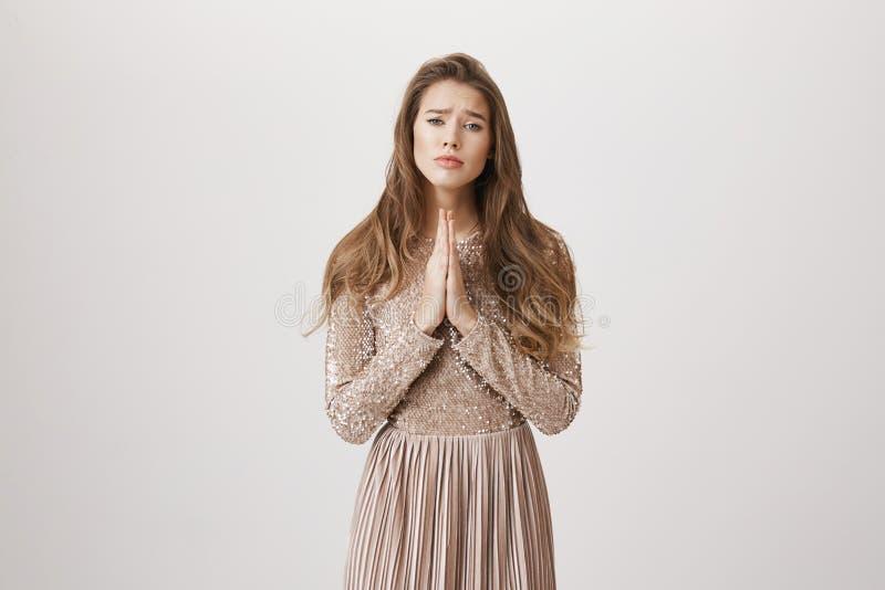 Retrato da mulher caucasiano louro encantador que mostra o pedido ou rezar do gesto, olhar de sobrancelhas franzidas e estar com  foto de stock royalty free