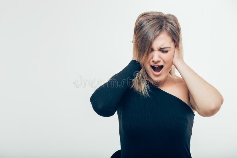 Retrato da mulher caucasiano que cobre suas orelhas sobre o fundo cinzento imagem de stock