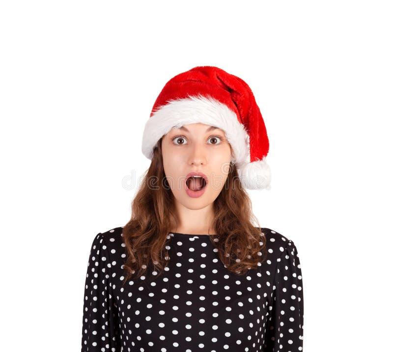 Retrato da mulher chocada e surpreendida expressivo menina emocional no chapéu do Natal de Papai Noel isolado no fundo branco Hol fotos de stock royalty free