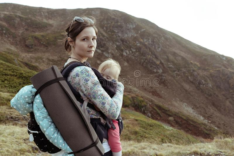 Retrato da mulher com bebê e da trouxa na montanha fotos de stock