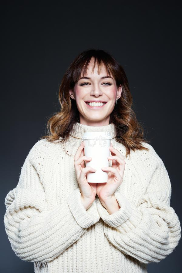 Retrato da mulher com cabelo longo com a xícara de café descartável afastada nas mãos, camiseta branca vestindo do inverno, backg foto de stock