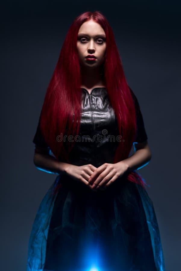 Retrato da mulher com cabelo vermelho e o vestido gótico preto fotografia de stock royalty free