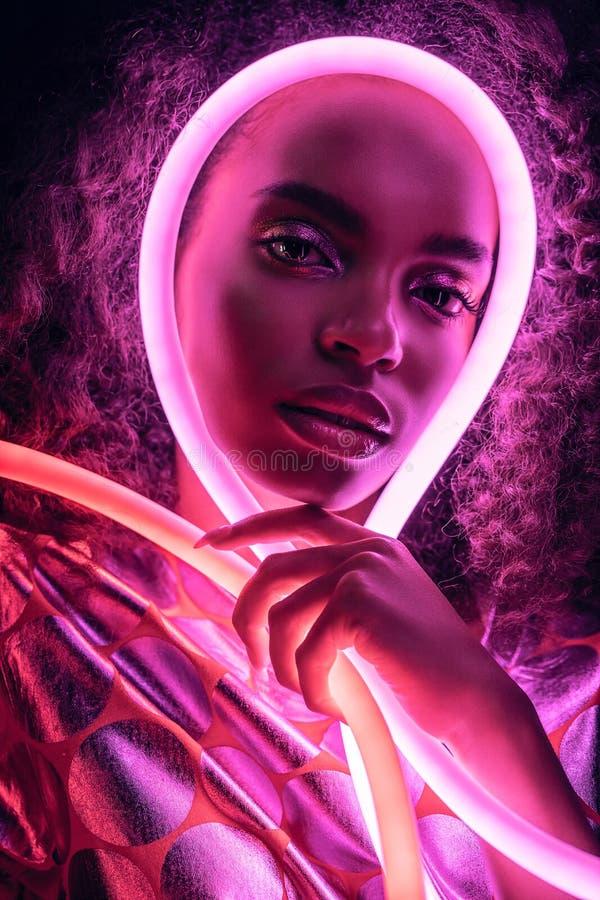 Retrato da mulher com luz néon rosa à volta da face imagem de stock