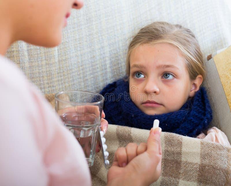 Retrato da mulher com o antibiótico e a criança que estão com a gripe imagem de stock royalty free