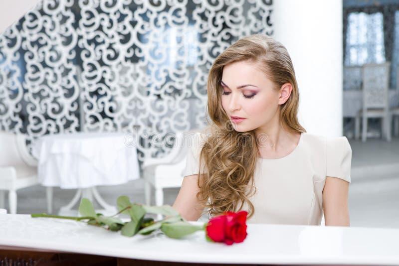Retrato da mulher com a rosa do vermelho que joga o piano fotos de stock royalty free