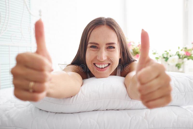 Retrato da mulher com sorriso largo na cama com mãos no coxim fotos de stock