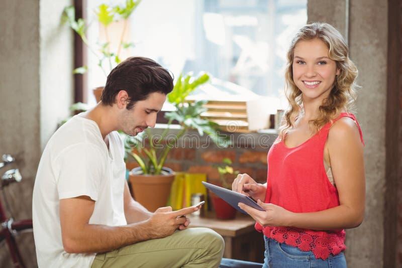 Retrato da mulher com tabuleta digital quando homem que usa o smartphone no escritório fotografia de stock