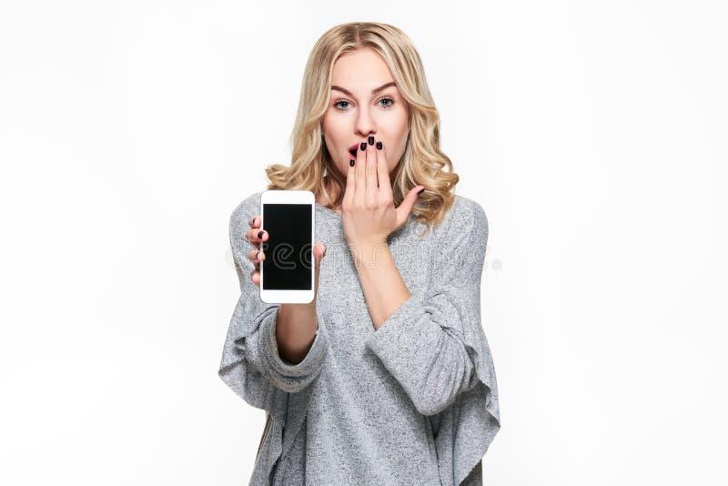 Retrato da mulher consideravelmente loura chocada com mão em sua boca que mostra a telefone celular a tela vazia isolada sobre o  fotos de stock