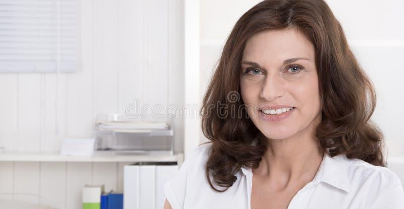 Retrato da mulher consideravelmente mais idosa no fundo branco foto de stock