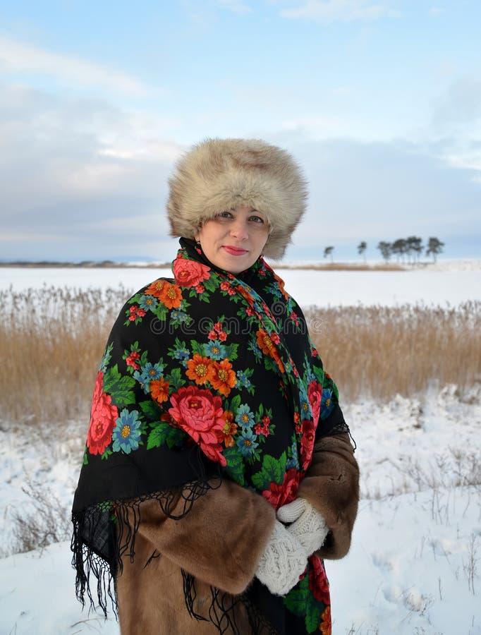 Retrato da mulher da Idade Média em um tampão da pele e em um xaile colorido contra o lago do inverno fotografia de stock royalty free