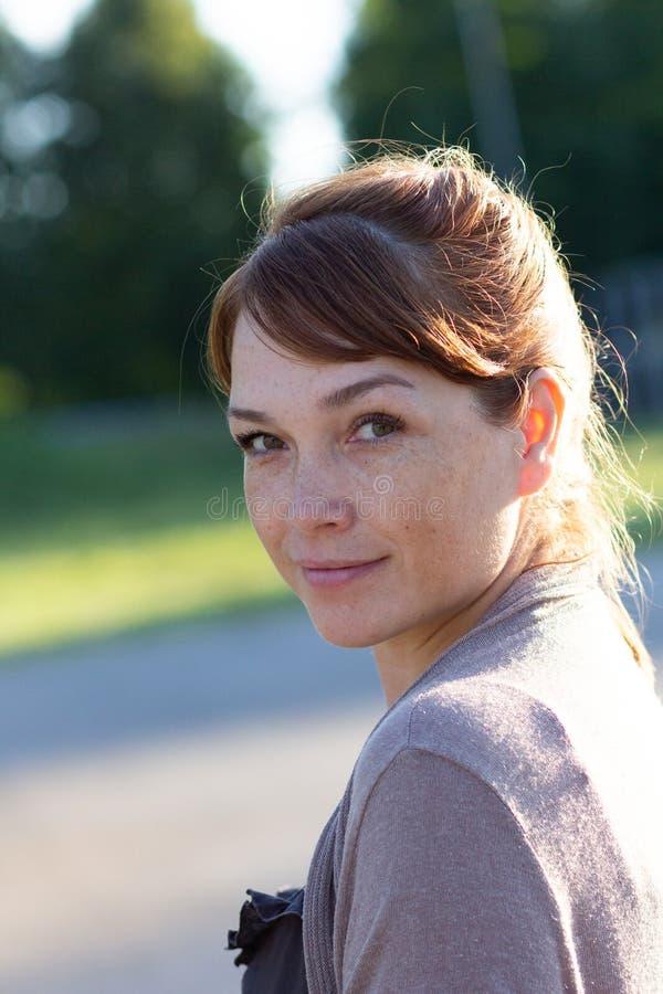 Retrato da mulher de meia idade bonita com a cara calma e sorrindo que olha a câmera no parque verde do verão imagens de stock royalty free