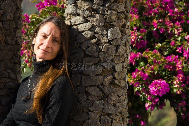Retrato da mulher de meia-idade por coluna de jardim fotos de stock