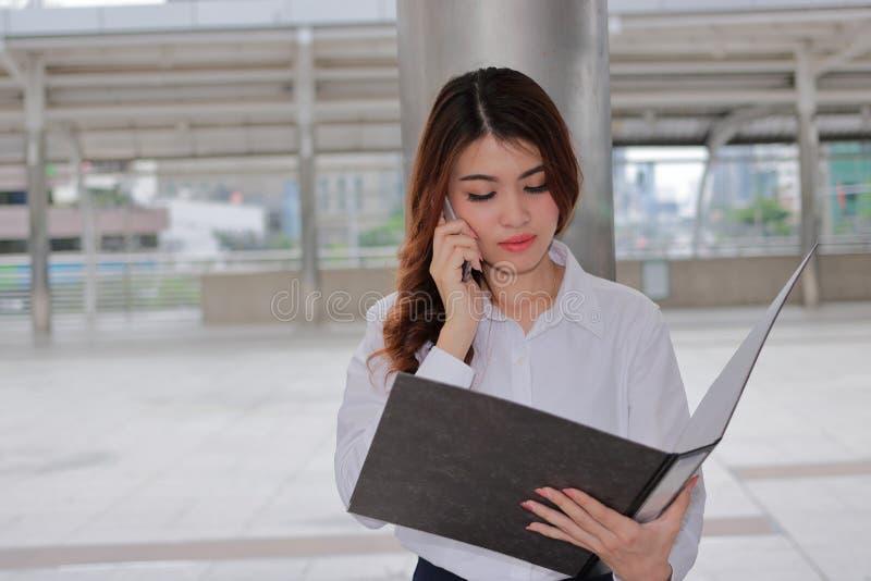 Retrato da mulher de negócio asiática atrativa nova que fala no telefone para seu trabalho no fundo exterior urbano imagens de stock royalty free