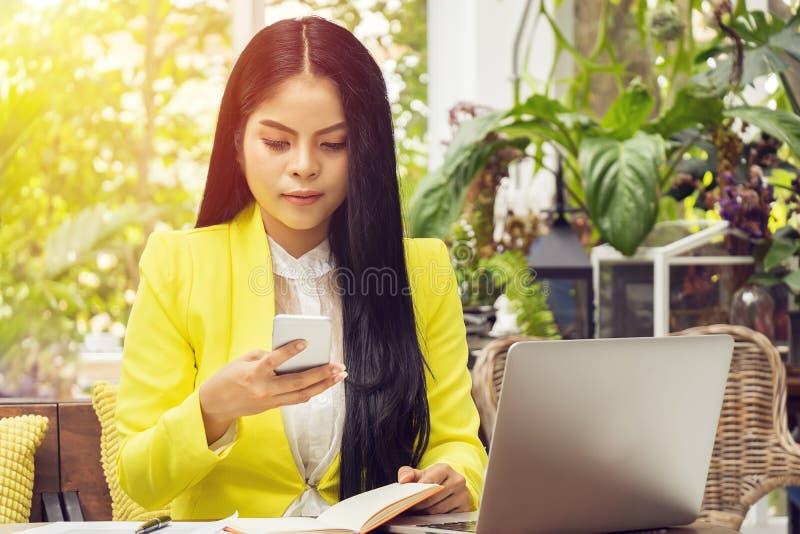 Retrato da mulher de negócio asiática bonita e segura que senta-se na frente do portátil do caderno e que verifica no telefone pa imagem de stock