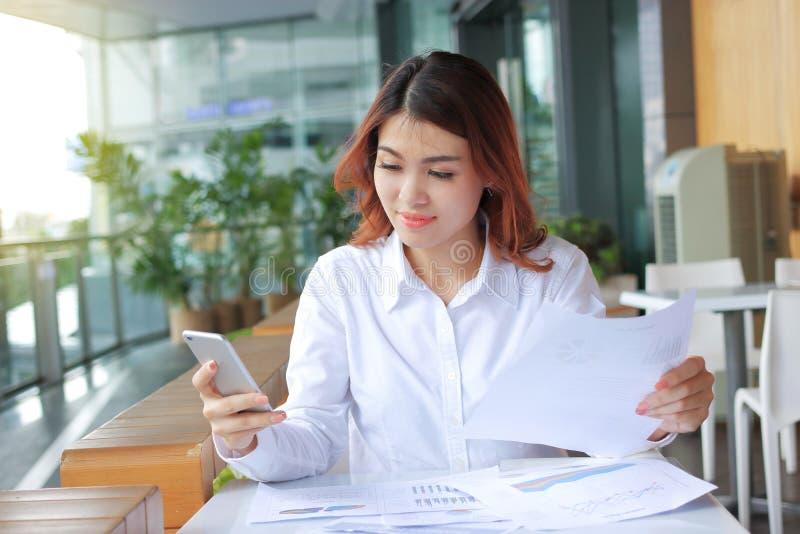 Retrato da mulher de negócio asiática nova atrativa que olha no telefone e que guarda cartas ou documento em sua mão na mesa no o foto de stock royalty free