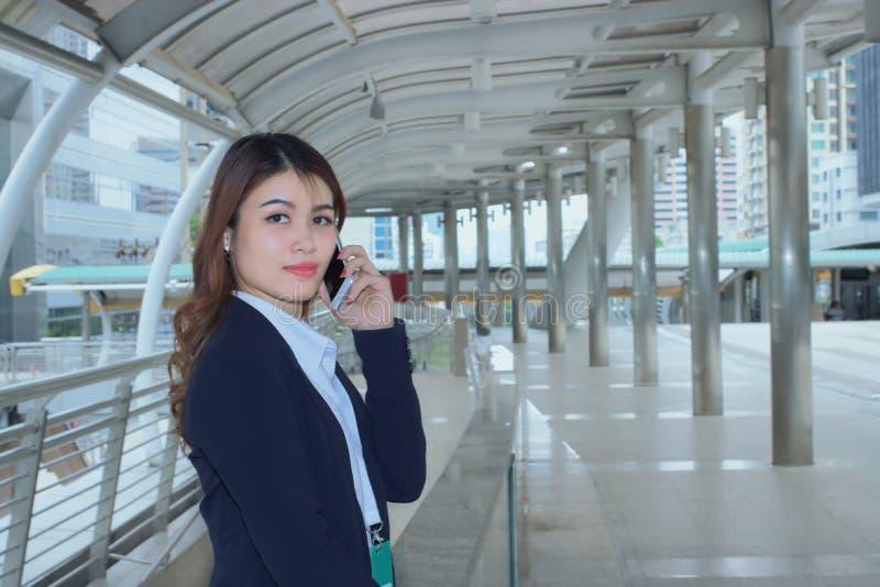 Retrato da mulher de negócio asiática nova da cara bonita que fala no telefone no fundo urbano da cidade imagem de stock