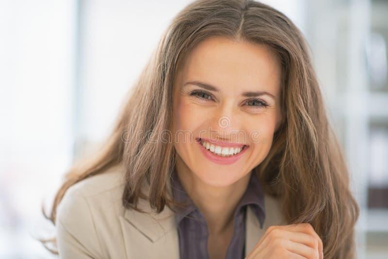 Retrato da mulher de negócio de sorriso no escritório imagem de stock