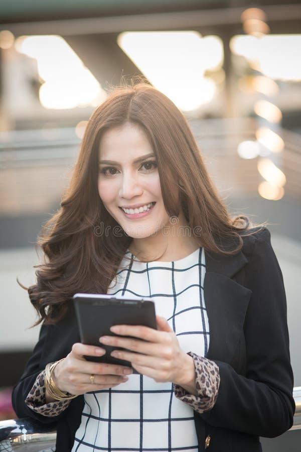 Retrato da mulher de negócio esperta bem sucedida que olha segura e que sorri guardando o tablet pc fotografia de stock royalty free