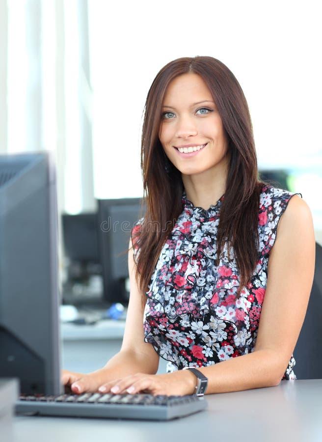 Retrato da mulher de negócio nova de sorriso que usa o computador imagens de stock