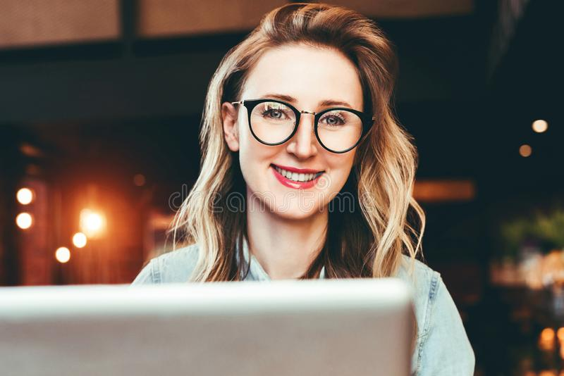 Retrato da mulher de negócio nova nos vidros na moda que sentam-se no café, trabalhando no portátil O Blogger comunica-se com os  fotografia de stock