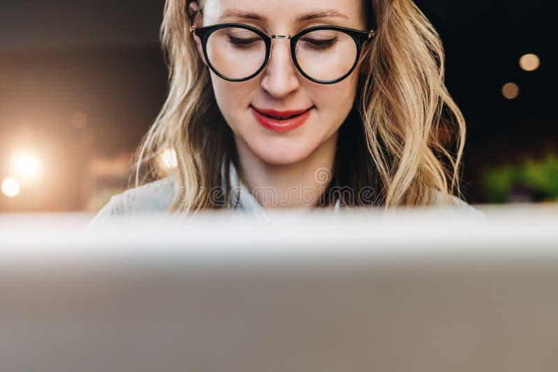 Retrato da mulher de negócio nova nos vidros na moda que sentam-se no café, trabalhando no portátil O Blogger comunica-se com os  imagem de stock royalty free