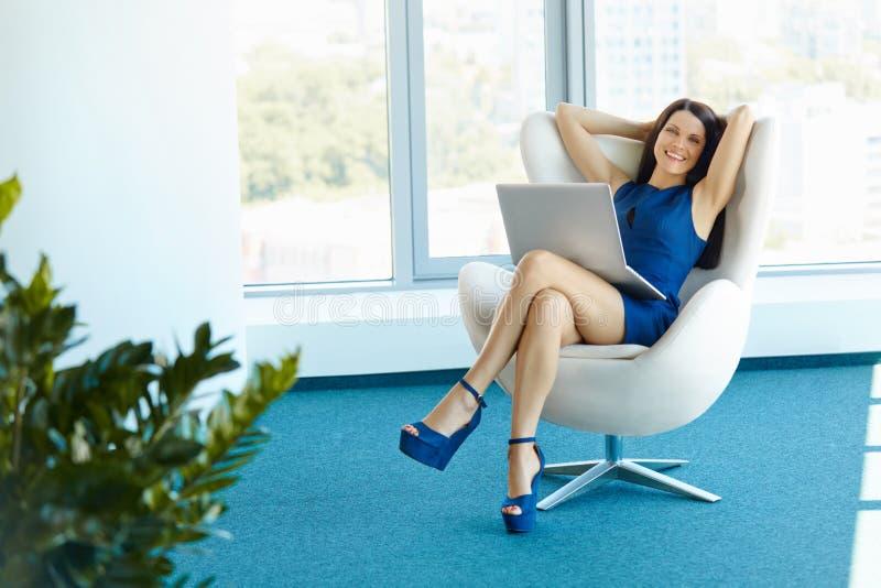 Retrato da mulher de negócio relaxado no escritório Relaxe e liberdade imagens de stock royalty free