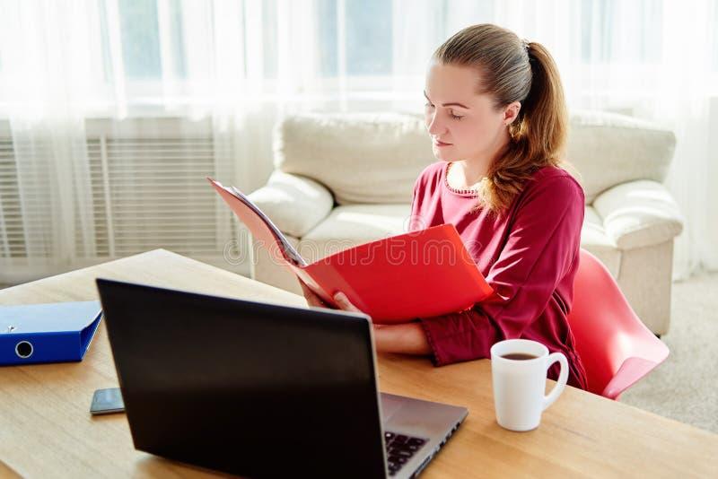 Retrato da mulher de negócio segura nova que senta-se na mesa de madeira com portátil e que trabalha com papel no escritório mode imagens de stock