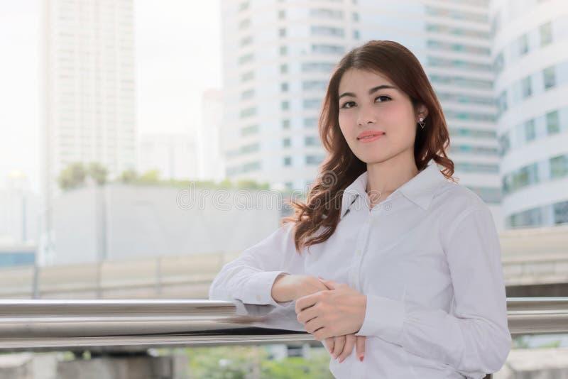 Retrato da mulher de negócios asiática nova atrativa que olha na câmera na construção urbana com fundo do efeito da luz do sol Li imagem de stock