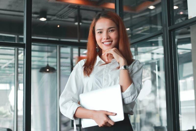 Retrato da mulher de negócios asiática nova de sorriso com o portátil que olha a câmera no escritório Pensamento e conceito pensa fotos de stock royalty free