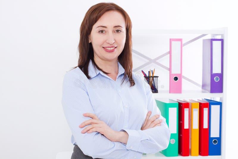 Retrato da mulher de negócios atrativa de sorriso no fundo do escritório isolado no branco Copie o espaço e zombe-o acima Foco se foto de stock