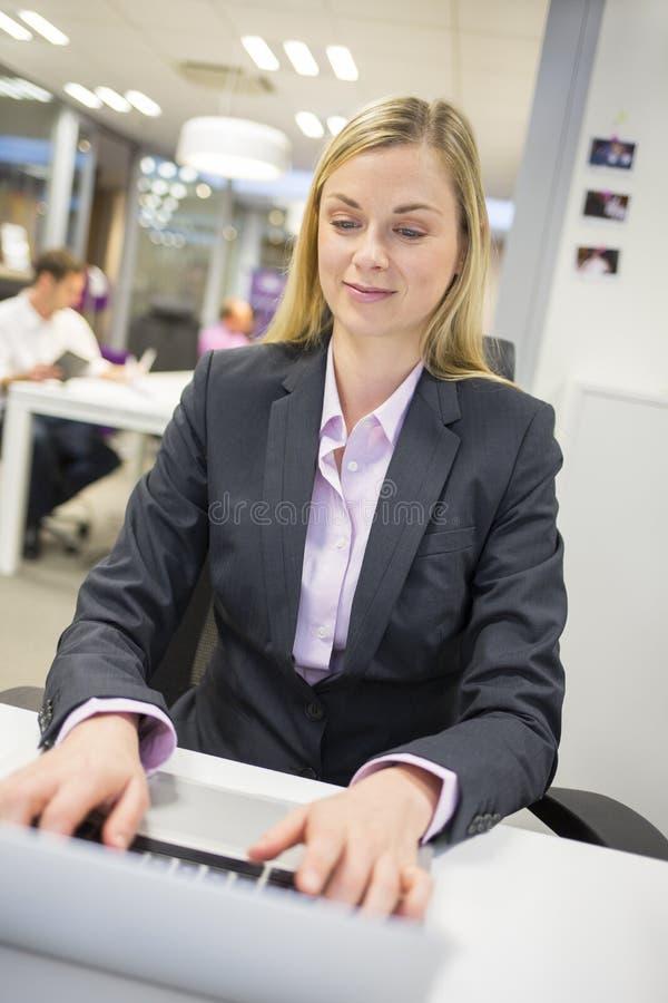 Retrato da mulher de negócios bem sucedida que trabalha com o portátil no offi fotografia de stock