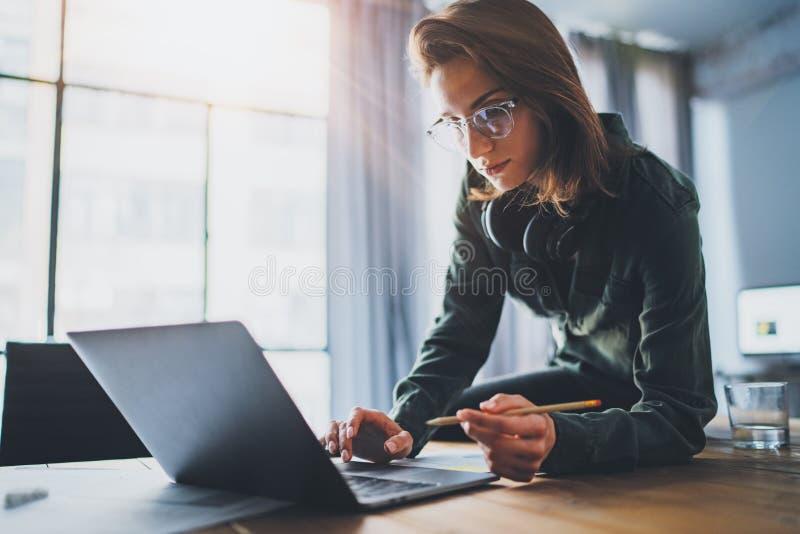 Retrato da mulher de neg?cios consider?vel nova que usa o laptop no escrit?rio moderno Fundo borrado fotografia de stock
