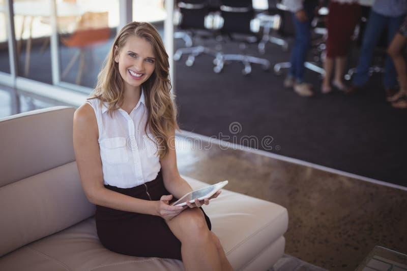 Retrato da mulher de negócios de sorriso que guarda a tabuleta digital ao sentar-se no sofá imagens de stock royalty free