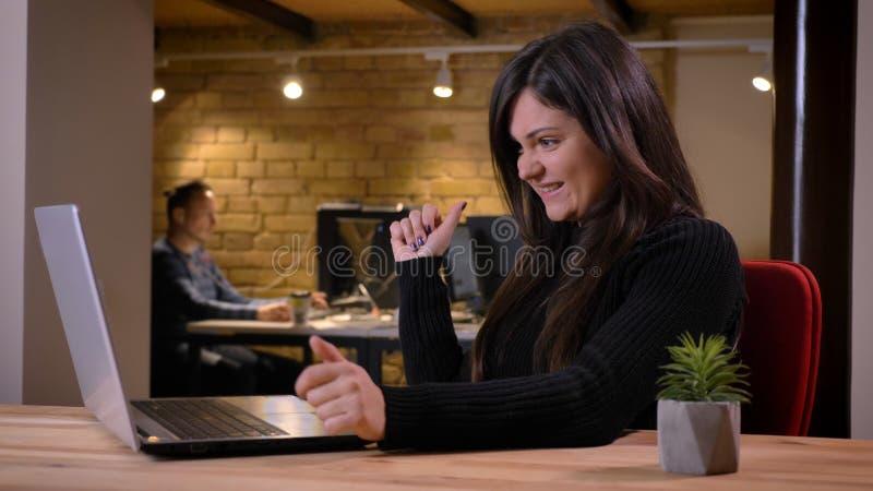 Retrato da mulher de negócios excesso de peso de meia idade que trabalha com portátil e que sorri para o sucesso no fundo do escr fotografia de stock royalty free