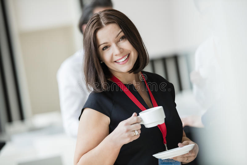 Retrato da mulher de negócios feliz que guarda o copo de café no salão do seminário foto de stock