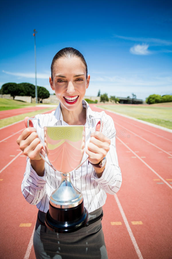 Retrato da mulher de negócios feliz que guarda um troféu imagens de stock