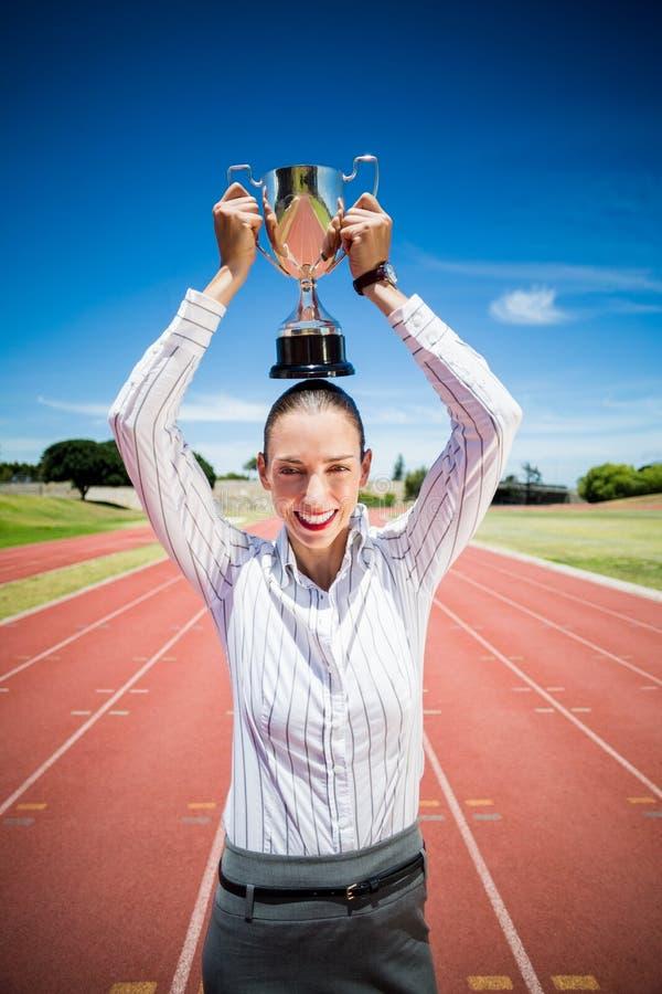 Retrato da mulher de negócios feliz que guarda um troféu sobre sua cabeça foto de stock