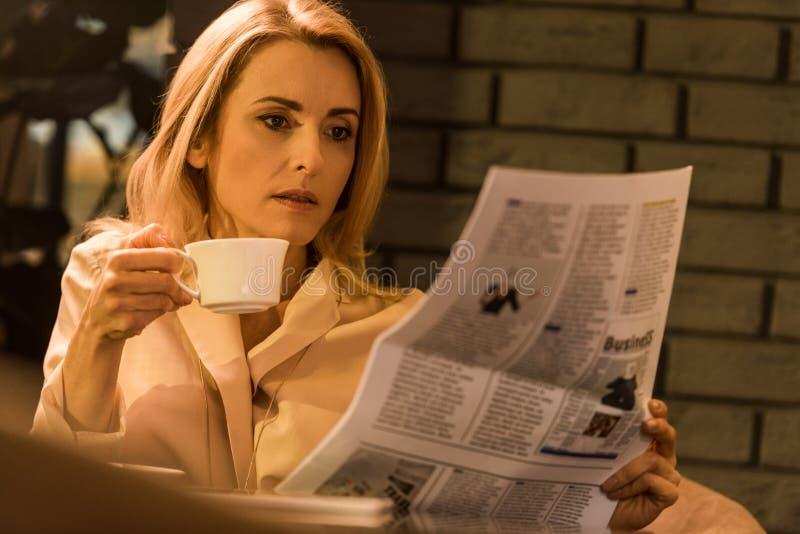retrato da mulher de negócios focalizada com o jornal da leitura da xícara de café imagens de stock