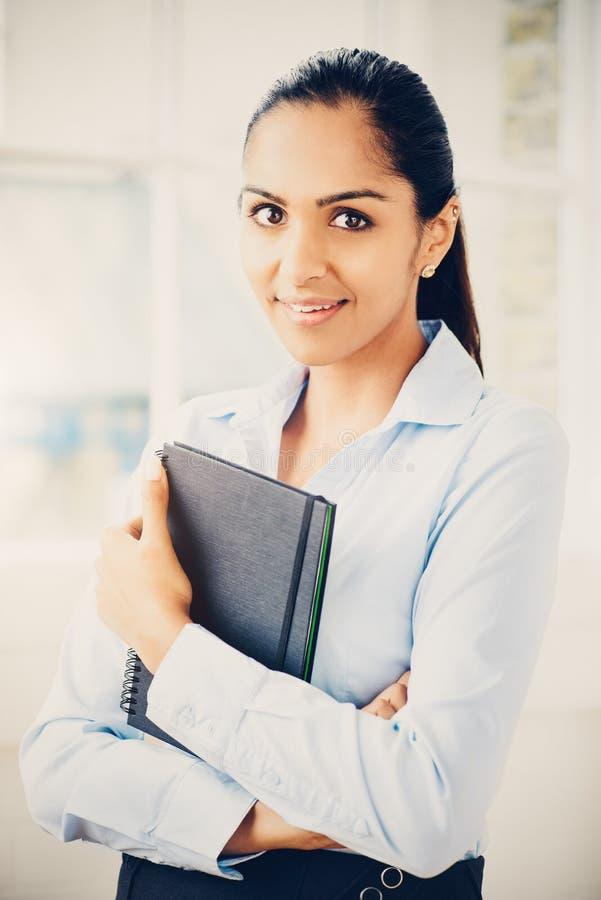 Retrato da mulher de negócios indiana atrativa que trabalha da casa imagem de stock