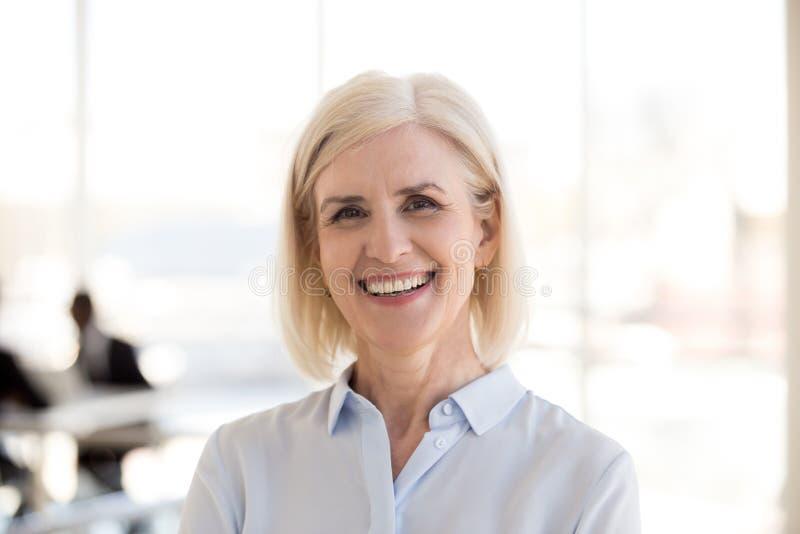 Retrato da mulher de negócios madura que levanta o sorriso na câmera imagens de stock