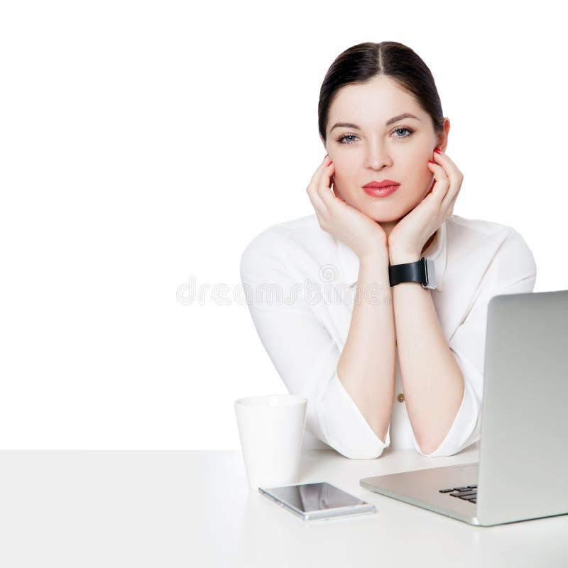 Retrato da mulher de negócios moreno atrativa calma com composição na camisa branca que senta-se com portátil, tocando em na sua  foto de stock royalty free
