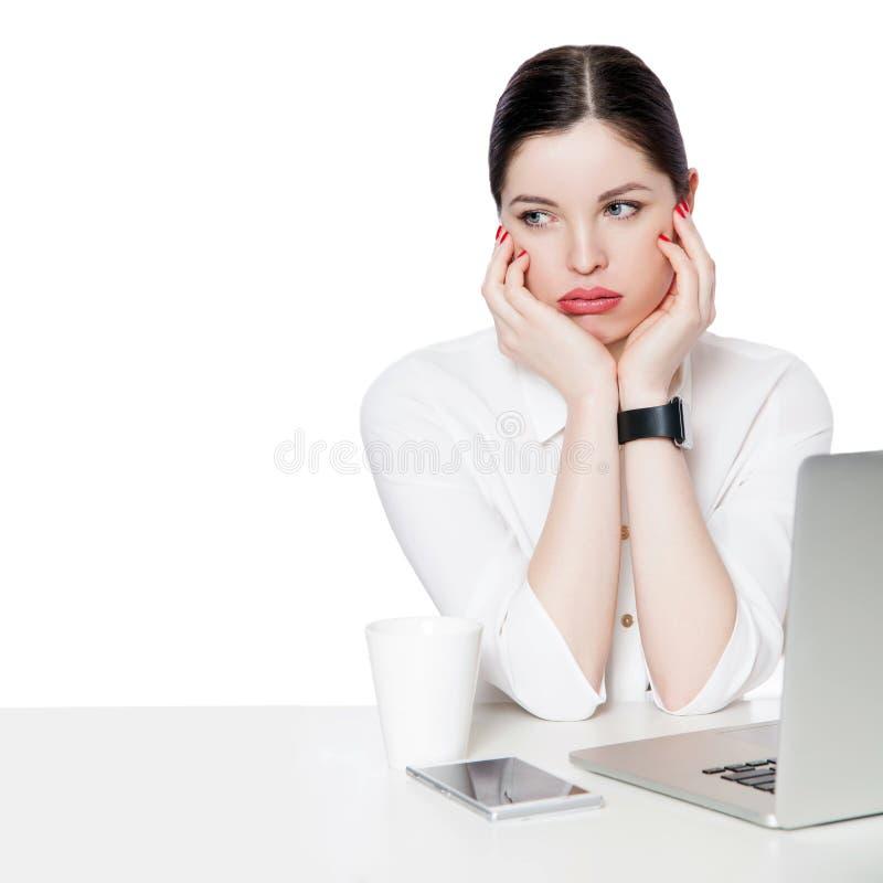 Retrato da mulher de negócios moreno pensativa na camisa branca que senta-se com portátil, tocando em sua cara, olhando afastado, fotos de stock royalty free