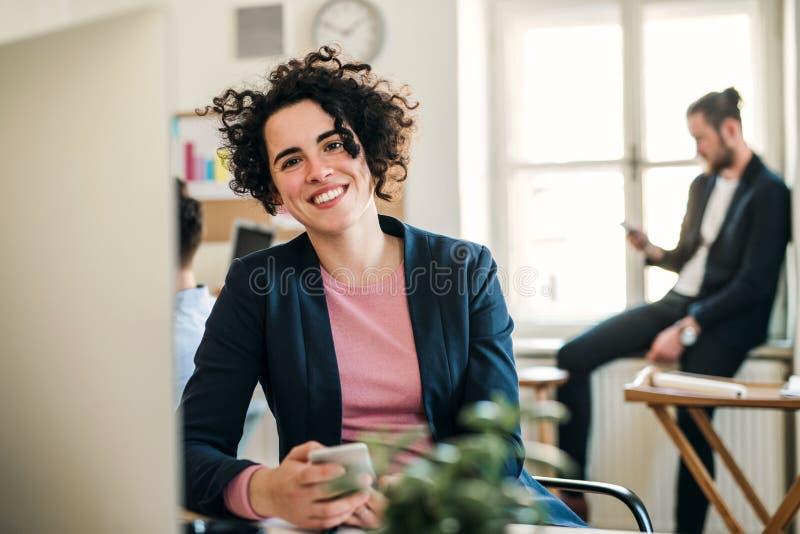 Retrato da mulher de negócios nova com colegas em um escritório moderno foto de stock