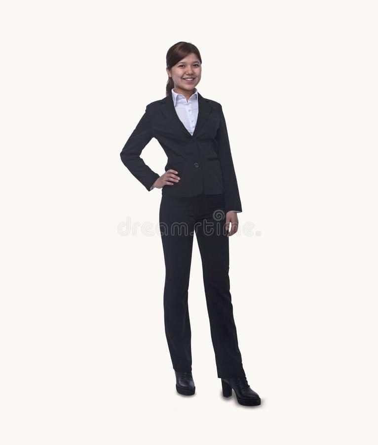 Retrato da mulher de negócios nova de sorriso com mão no quadril que olha a câmera, comprimento completo, tiro do estúdio fotografia de stock royalty free