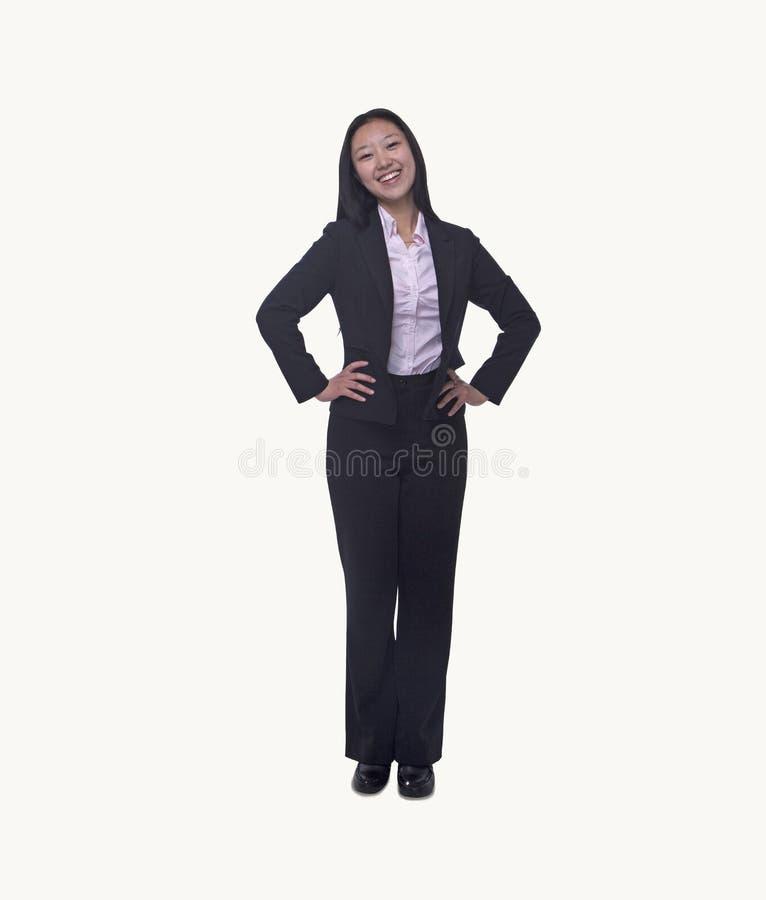 Retrato da mulher de negócios nova de sorriso com mãos nos quadris que olham a câmera, comprimento completo, tiro do estúdio foto de stock